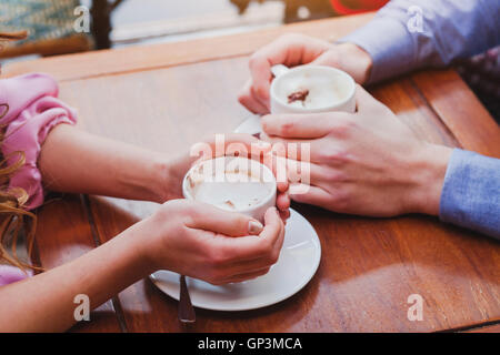 people drinking coffee in cafe, closeup of couple hands with cups - Stock Photo