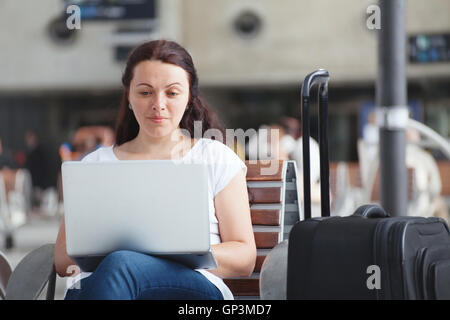 woman with laptop in airport, using internet connection, traveler checking email - Stock Photo