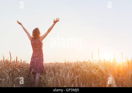 breathing, woman with raised hands enjoying sunset in the field - Stock Photo