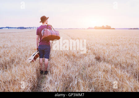 young son leaving home, romantic travel background, man with guitar and road bag walking at sunset field - Stock Photo