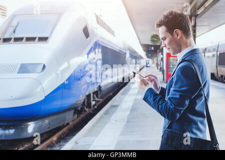 man using mobile application on his smartphone at train station, business travel - Stock Photo
