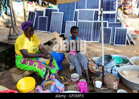 BURKINA FASO, Provinz Poni, Gaoua, weekly market with food crops and solar panels, girl playing with mobile phone - Stock Photo