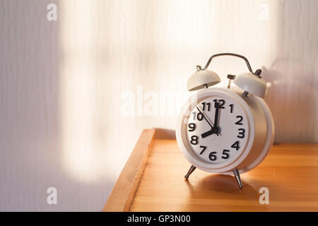 eight o'clock in the morning, alarm clock on bedside table - Stock Photo