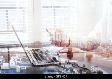 double exposure of hands of business man using smartphone in the office, London cityscape - Stock Photo