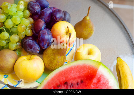 plate with fruits - apples, pears, plums, grapes. healthy food concept - Stock Photo
