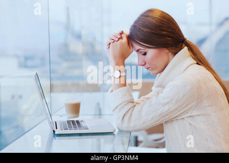information overload, stress concept, sad desperate woman in front of computer - Stock Photo