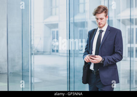 businessman using smartphone near office building - Stock Photo