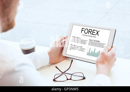 forex, businessman reading about foreign exchange market on tablet - Stock Photo