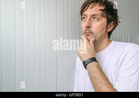 Man with hand on chin thinking deep thoughts and making tough decisions - Stock Photo