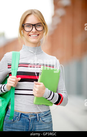 girl holding her tablet in campus park - Stock Photo