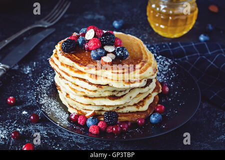 Delicious pancakes with fresh berries and honey on dark slate background, close up view - Stock Photo