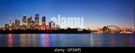 panorama of Sydney city CBD and major landmarks around harbour to Harbour Bridge and North Sydney. Illuminated buildings - Stock Photo
