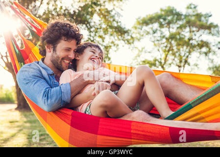Father and son relaxing together in hammock - Stock Photo
