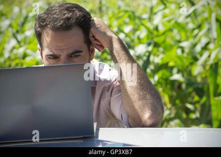 Man using laptop computer outdoors - Stock Photo