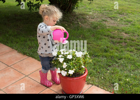 Little girl watering potted plants - Stock Photo