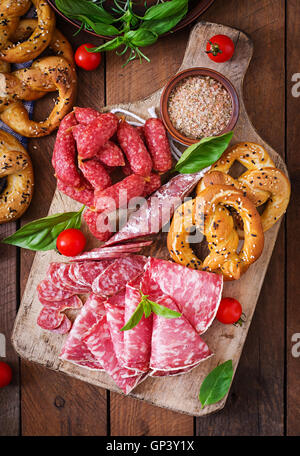 Pretzels and various sausages on wooden background. Oktoberfest. - Stock Photo