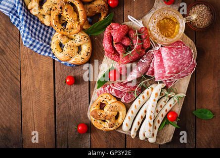 Glass of beer, pretzels and various sausages on wooden background. Oktoberfest. Top view - Stock Photo