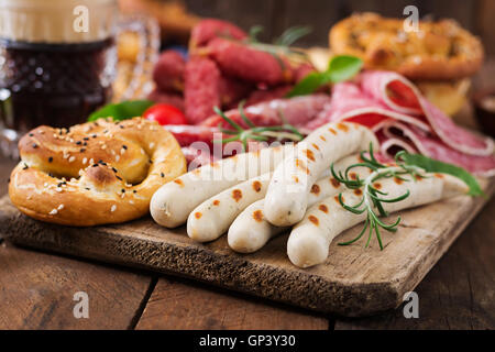 Glass of beer, pretzels and various sausages on wooden background. Oktoberfest. - Stock Photo