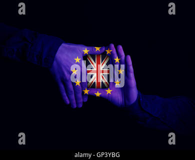 Close up of hands patterned with the flag of the European Community holding a card with the flag of the United Kingdom. - Stock Photo