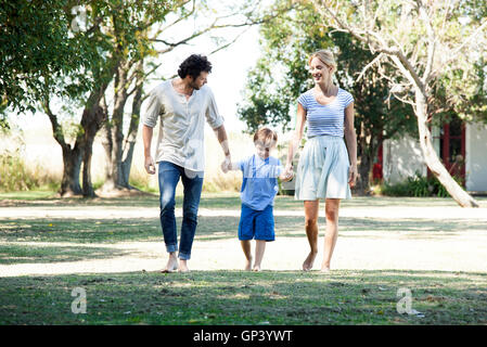 Family with one child taking walk outdoors together - Stock Photo