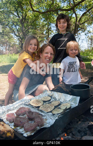Mother and children grilling together at campsite - Stock Photo