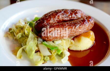 Sausage and mashed potato with seasonal greens served with red wine gravy on a white plate - filter applied - Stock Photo