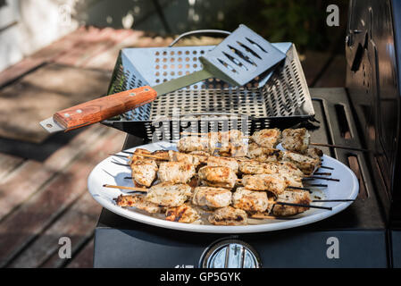 Chicken skewers on a white plate after grilling (Souvlaki) - Stock Photo