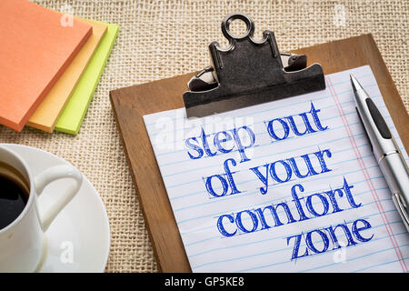 Step out of your comfort zone text on clipboard  with a pen, coffee and sticky notes against burlap canvas - office abstract