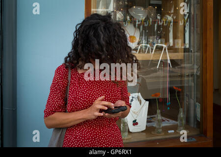 A woman in a red dress, with her face covered by her hair, is busy on her smart mobile phone - Plymouth, 1st September 2016