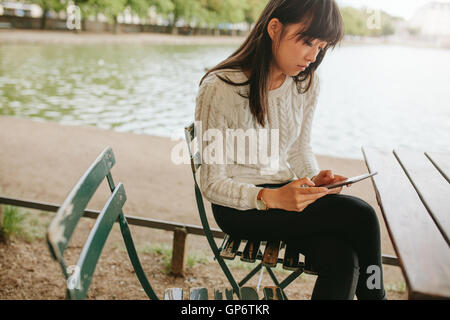 Shot of chinese woman at outdoor cafe by the pond using digital tablet. Young woman reading ebook on her digital - Stock Photo