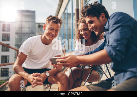 Group of people watching video on the mobile phone while sitting at outdoor cafe. Three young friends sitting outdoors - Stock Photo