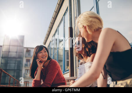 Group of female friends talking in a terrace. Three young women meeting at outdoor cafe chatting and enjoying. - Stock Photo