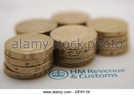 File photo dated 27/01/15 of pound coins next to the HM Revenue & Customs logo. Corporation tax should be scrapped - Stock Photo