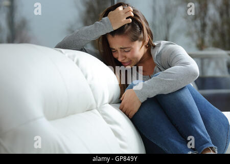 Sad girl crying desperately alone sitting on a couch at home in a dark winter day - Stock Photo