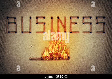 Burning match setting fire to its neighbors in arranged in shape of business word. Ignited match stick  as a symbol - Stock Photo
