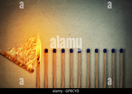 Burning match setting fire to its whole neighbors, a metaphor for ideas and inspiration. Leadership concept - Stock Photo