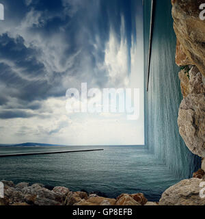 Surreal background of two worlds collide at the coast of the sea. Sea landscape between two piers on the stone beach - Stock Photo