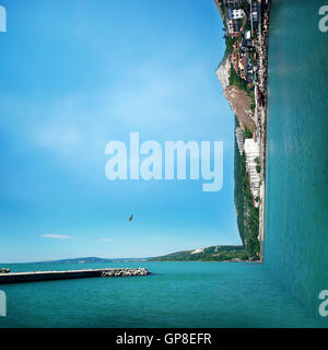 Surreal background of two worlds collide at the coast of the sea. Sea landscape journey and vacation concept. - Stock Photo