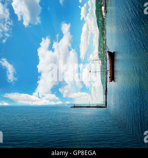 Surreal background of two worlds collide at the coast of the sea. Clear morning view with a sail boat floating. - Stock Photo