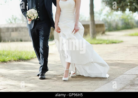 Bride and groom walking together in a park in wedding day - Stock Photo