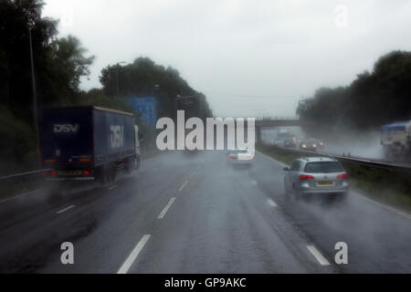 driving in middle lane on UK motorway in poor wet conditions surrounded by trucks and cars - Stock Photo