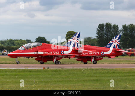 Royal Air Force (RAF) Red Arrows aerobatic display team flying British Aerospace Hawk jet trainer aircraft. - Stock Photo