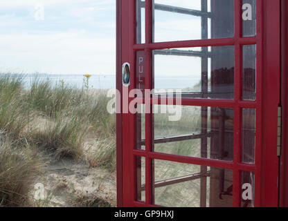 Red telephone box on Studland beach, Dorset, England. - Stock Photo