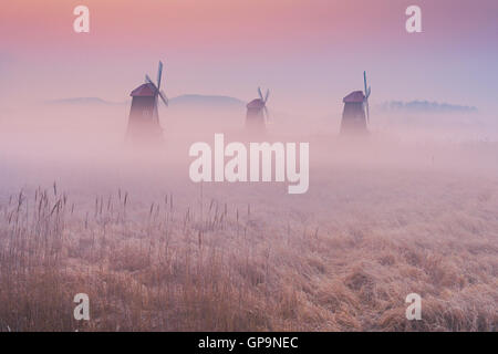 autumn landscape misty morning on the wooden windmills in the park. - Stock Photo