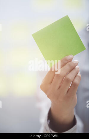 Woman holding sticky note with empty space - Stock Photo