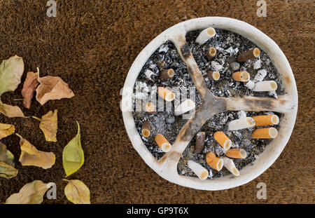 White pottery handmade ashtray full of a huge number of cigarettes and ashes on a background of sackcloth and dead - Stock Photo