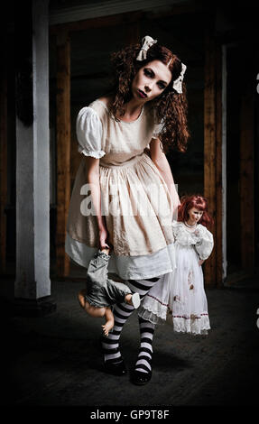 The strange scary girl with dolls in hands - Stock Photo