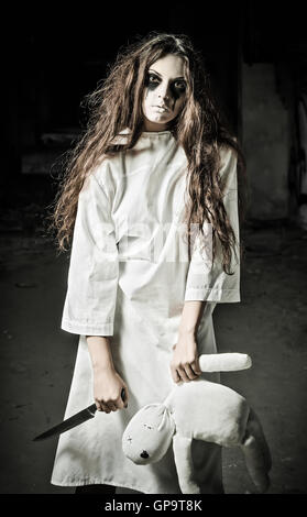 Horror style shot: a strange sad girl with moppet doll and knife in hands - Stock Photo