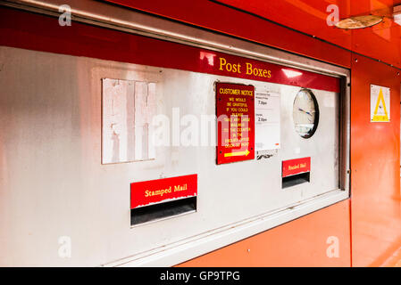 Letter box at a main Royal Mail sorting office, including boxes for franked and stamped post. - Stock Photo