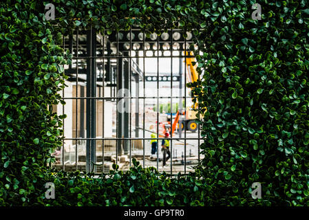 A viewing window on hoarding at a building site, which has been covered with plastic vegetation to improve its look - Stock Photo